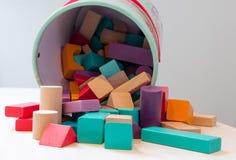 Οι φραγμοί παιχνιδιών, πολύχρωμα ξύλινα τούβλα, ζωηρόχρωμα κομμάτια παιχνιδιών οικοδόμησης παιδιών των παιδιών οργανώνουν το παιχ στοκ φωτογραφία