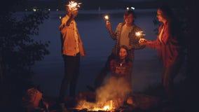 Οι φροντίζοντας τουρίστες φίλων συγχαίρουν το κορίτσι στο φέρνοντας κέικ γενεθλίων και καίγοντας Βεγγάλη τα φω'τα, η γυναίκα φυσά απόθεμα βίντεο