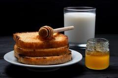 Οι φρυγανιές σε ένα άσπρο πιάτο με ένα μέλι μετακινούν με το κουτάλι, αρμέγουν και ένα μέλι μπορεί Στοκ φωτογραφία με δικαίωμα ελεύθερης χρήσης