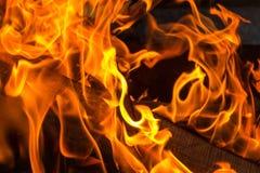 Οι φωτεινές πορτοκαλιές γλώσσες φλογών πυρκαγιάς απορροφούν το καυσόξυλο Στοκ φωτογραφία με δικαίωμα ελεύθερης χρήσης