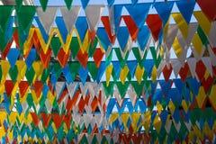 Οι φωτεινές χρωματισμένες τριγωνικές σημαίες κρεμούν πολύ μαζί από τη γραμμή στοκ εικόνα