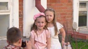 Οι φωτογραφίες μικρών παιδιών στην παλαιά κάμερα των αδελφών σε έναν αναδρομικό στα ενδύματα απόθεμα βίντεο