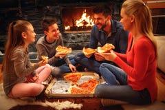 Οι χαμογελώντας γονείς και τα παιδιά έχουν τη διασκέδαση και την κατανάλωση της πίτσας στοκ εικόνες