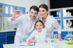 Οι χαμογελώντας επιστήμονες που εργάζονται με το μικροσκόπιο γλιστρούν μέσα το εργαστήριο στοκ εικόνες