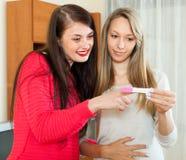 Οι χαμογελώντας φίλες με την εγκυμοσύνη εξετάζουν στοκ εικόνα