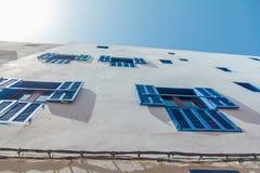 Οι χαρακτηριστικοί τοίχοι των σπιτιών με τα μπλε παράθυρα στην ΟΥΝΕΣΚΟ προστάτευσαν την παλαιά αραβική πόλη Essaouira Στοκ Φωτογραφία