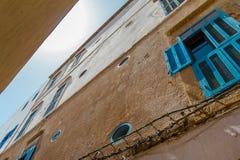 Οι χαρακτηριστικοί τοίχοι των σπιτιών με τα μπλε παράθυρα στην ΟΥΝΕΣΚΟ προστάτευσαν την παλαιά αραβική πόλη Essaouira Στοκ Εικόνες
