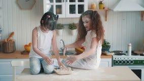Οι χαριτωμένες αδελφές που ρίχνουν το αλεύρι η μια στην άλλη, έχουν το χρόνο διασκέδασης στην κουζίνα, σε αργή κίνηση φιλμ μικρού μήκους