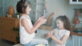Οι χαριτωμένες αδελφές που ρίχνουν το αλεύρι η μια στην άλλη, έχουν το χρόνο διασκέδασης στην κουζίνα, σε αργή κίνηση απόθεμα βίντεο