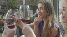Οι χαριτωμένες φίλες που κουβεντιάζουν στο εστιατόριο, ξοδεύουν το χρόνο από κοινού Κομψή γυναίκα με μακρυμάλλη λέγοντας την ιστο απόθεμα βίντεο