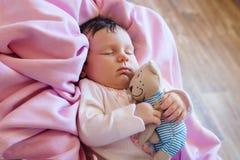 Οι χαριτωμένοι νεογέννητοι ύπνοι μωρών με ένα παιχνίδι teddy αντέχουν Στοκ εικόνα με δικαίωμα ελεύθερης χρήσης