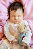 Οι χαριτωμένοι νεογέννητοι ύπνοι μωρών με ένα παιχνίδι teddy αντέχουν Στοκ Εικόνες