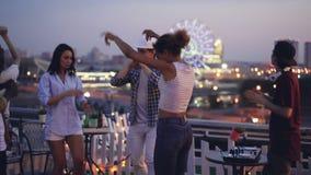 Οι χαρούμενοι νέοι έχουν το κόμμα στη στέγη που χορεύει και που γελά ενώ ο deejay εύθυμος νεαρός άνδρας εργάζεται με απόθεμα βίντεο
