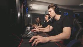 Οι χαρούμενοι νέοι που κάθονται στους ισχυρούς υπολογιστές στο τυχερό παιχνίδι στρέφονται και που δίνουν υψηλά πέντε triumphantly απόθεμα βίντεο