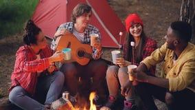 Οι χαρούμενοι φίλοι νέων τα γυαλιά με τα ποτά καθμένος την πυρκαγιά στο δάσος με θερμό marshmallow επάνω φιλμ μικρού μήκους