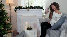 Οι χειμερινές διακοπές, κορίτσι που διαβάζουν ένα βιβλίο, γυναίκα πίνουν το τσάι από ένα φλυτζάνι, στα άνετα ενδύματα, καθμένος α φιλμ μικρού μήκους