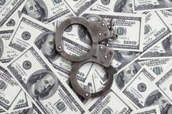 Οι χειροπέδες αστυνομίας βρίσκονται σε πολλούς λογαριασμούς δολαρίων Η έννοια της παράνομης κατοχής των χρημάτων, παράνομες συναλ στοκ φωτογραφίες