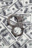 Οι χειροπέδες αστυνομίας βρίσκονται σε πολλούς λογαριασμούς δολαρίων Η έννοια της παράνομης κατοχής των χρημάτων, παράνομες συναλ στοκ φωτογραφίες με δικαίωμα ελεύθερης χρήσης
