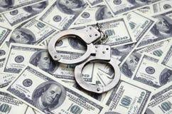 Οι χειροπέδες αστυνομίας βρίσκονται σε πολλούς λογαριασμούς δολαρίων Η έννοια της παράνομης κατοχής των χρημάτων, παράνομες συναλ στοκ εικόνα με δικαίωμα ελεύθερης χρήσης