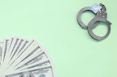 Οι χειροπέδες αστυνομίας και οι εκατοντάδες των αμερικανικών δολαρίων βρίσκονται σε ένα υπόβαθρο ασβέστη στοκ φωτογραφία με δικαίωμα ελεύθερης χρήσης