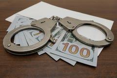 Οι χειροπέδες βρίσκονται σε έναν φάκελο στον οποίο είναι πολλοί λογαριασμοί εκατό δολαρίων καφετής ξύλινος ανασκόπησης Παραβίαση  στοκ εικόνα