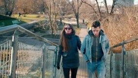 Οι χιλιετείς άνθρωποι συνδέουν: Ο φίλος και η φίλη περπατούν επάνω στο πάρκο φιλμ μικρού μήκους