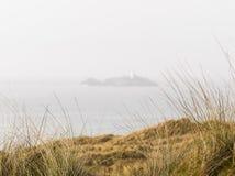 Οι χλόες στη βρετανική ακτή με ο φάρος στο υπόβαθρο στοκ εικόνες