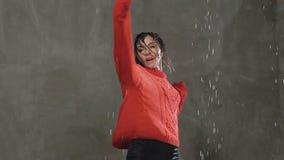 Οι χοροί κοριτσιών στη βροχή Υγρός θηλυκός χορευτής κύκλους στους κόκκινους πουλόβερ γύρω από τον κάτω από τις πτώσεις της βροχής φιλμ μικρού μήκους