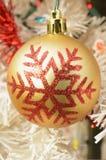 Οι χρυσές διακοσμήσεις Χριστουγέννων με το κόκκινο ακτινοβολούν snowflake σχέδιο Στοκ φωτογραφία με δικαίωμα ελεύθερης χρήσης