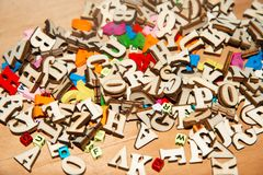Οι χρωματισμένες πλαστικές και ξύλινες επιστολές είναι σε έναν σωρό στοκ εικόνα