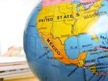 Οι χώρες και οι ήπειροι κλείνουν επάνω με το χάρτη χρώματος σε μια σφαίρα με τα βιβλία στο υπόβαθρο στοκ φωτογραφία