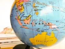 Οι χώρες και οι ήπειροι κλείνουν επάνω με το χάρτη χρώματος σε μια σφαίρα με τα βιβλία στο υπόβαθρο στοκ εικόνες