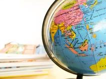 Οι χώρες και οι ήπειροι κλείνουν επάνω με το χάρτη χρώματος σε μια σφαίρα με τα βιβλία στο υπόβαθρο στοκ εικόνες με δικαίωμα ελεύθερης χρήσης
