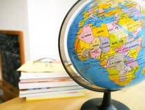 Οι χώρες και οι ήπειροι κλείνουν επάνω με το χάρτη χρώματος σε μια σφαίρα με τα βιβλία στο υπόβαθρο στοκ φωτογραφίες με δικαίωμα ελεύθερης χρήσης
