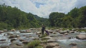 Οι ψαράδες άποψης Flycam βάζουν τα πιασμένα ψάρια στην τσάντα μεταξύ των ορμητικά σημείων ποταμού απόθεμα βίντεο