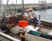 οι ψαράδες ξεφορτώνουν τη σύλληψή τους Στοκ Εικόνες