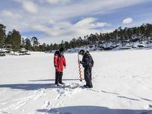 Οι ψαράδες πάγου με έναν πάγο χεριών τρυπούν Στοκ Εικόνα