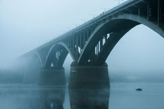 Οι ψαράδες σε μια βάρκα πλέουν κάτω από τη γέφυρα στην ομίχλη Στοκ φωτογραφία με δικαίωμα ελεύθερης χρήσης