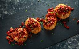 Οι ψημένες πατάτες σακακιών που ολοκληρώθηκαν με τα κόκκινα φασόλια kedney στη σάλτσα ντοματών και τα φρέσκα κρεμμύδια εξυπηρέτησ Στοκ Φωτογραφίες