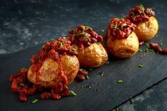 Οι ψημένες πατάτες σακακιών που ολοκληρώθηκαν με τα κόκκινα φασόλια kedney στη σάλτσα ντοματών και τα φρέσκα κρεμμύδια εξυπηρέτησ Στοκ Εικόνες