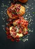 Οι ψημένες πατάτες σακακιών που ολοκληρώθηκαν με τα κόκκινα φασόλια kedney στη σάλτσα ντοματών και τα φρέσκα κρεμμύδια εξυπηρέτησ Στοκ Εικόνα