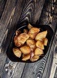 Οι ψημένες σφήνες πατατών με το σκόρδο, Χριστούγεννα διακοσμούν στοκ εικόνες