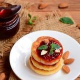Οι ψημένες τηγανίτες τυριών εξοχικών σπιτιών με το μούρο φράσσουν, αμύγδαλα και μέντα σε ένα άσπρο πιάτο Συνταγή Syrniki Στοκ φωτογραφία με δικαίωμα ελεύθερης χρήσης