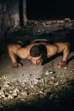 Οι ωθήσεις αθλητών, συμπιέσεις από το πάτωμα, είναι ισχυρός και σκληραγωγημένος στοκ εικόνες
