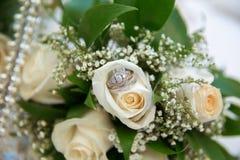 Οι όμορφες άσπρες γαμήλιες ανθοδέσμες στα λουλούδια ανθοδεσμών καλαθιών backgraound αυξήθηκαν/τα γαμήλια δαχτυλίδια Στοκ Εικόνα