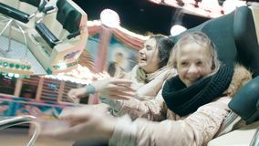 Οι όμορφες αδελφές οδηγούν μια έλξη περιστροφής σε ένα λούνα παρκ Οι νέες γυναίκες χορεύουν σε μια έλξη φιλμ μικρού μήκους