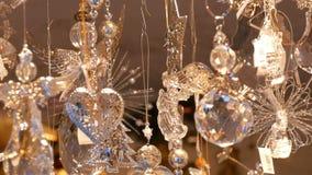 Οι όμορφες λεπτές λεπτές διακοσμήσεις παιχνιδιών Χριστουγέννων φιαγμένες από γυαλί και πορσελάνη υπό μορφή αγγέλων ταλαντεύονται  απόθεμα βίντεο