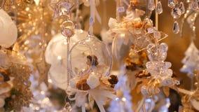 Οι όμορφες λεπτές λεπτές διακοσμήσεις παιχνιδιών Χριστουγέννων φιαγμένες από γυαλί και πορσελάνη υπό μορφή αγγέλων ταλαντεύονται  φιλμ μικρού μήκους