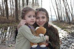 Οι όμορφες μικρές αδελφές θέτουν με τη teddy αρκούδα Στοκ Φωτογραφίες