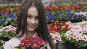 Οι όμορφες μυρωδιές κοριτσιών ανθίζουν με το χαμόγελο, θέτουν και εξετάζουν τη κάμερα φιλμ μικρού μήκους